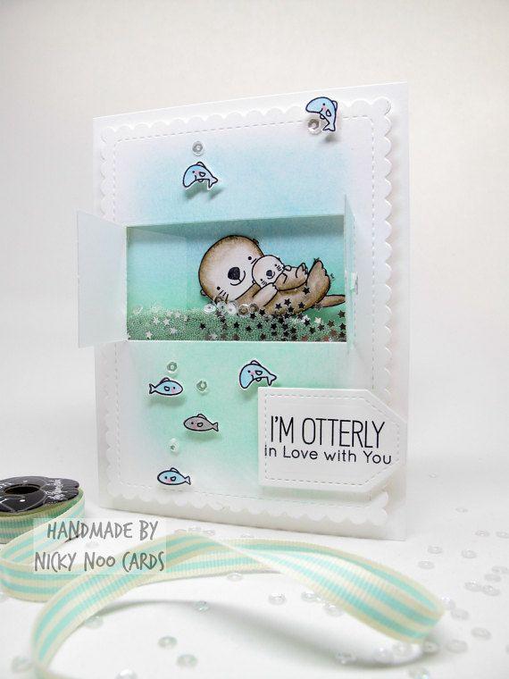 Handgemaakte Shaker Card - Otters - ik ben Otterly In liefde met u  Dit is een volledig handgemaakte kaart gebouwd met behulp van hoge kwaliteit 110lb zonne-wit karton voor een zeer stevige kaart. Een panel was die-cut met behulp van een gestikt en gegratineerde scherpe beïnvloeden. Dit paneel was inkt gemengd tot een zachte, waterige scène en vervolgens werd sterven gesneden nogmaals om het venster te openen. De otters en vis waren hand gestempeld met archival inkt, waterverf geschilderd en…