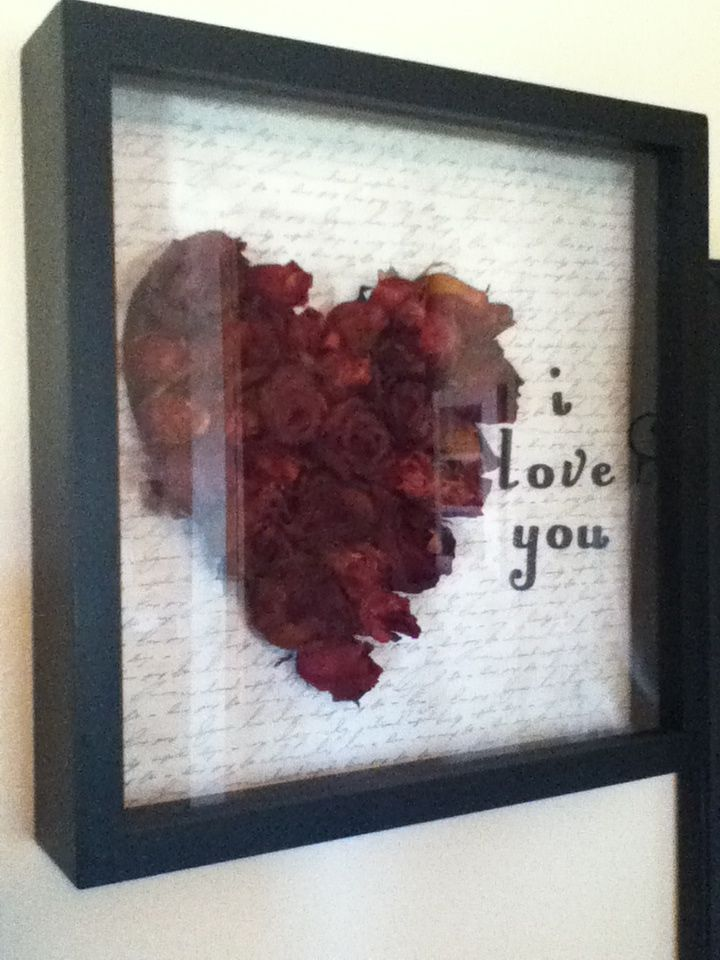 "Dried Roses idea! I had 2 bouquets of dried roses and cut them down to the bottom of the flower. I arranged them in a heart before I glued them onto the scrapbook paper. My scrapbook paper is black and white and looks like a letter and then I added the ""I love you"" (you can put anything). I then put it in a shadow box purchased from Hobby Lobby."