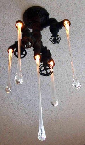 Awesome chandelier, old school pipes with blown glass lit up with leds. Looks like water falling from the spouts!