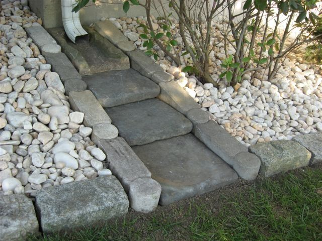 I love this idea, I would just like river rock, white rock is not my favorite.  Stone Rain Gutter Splash Block