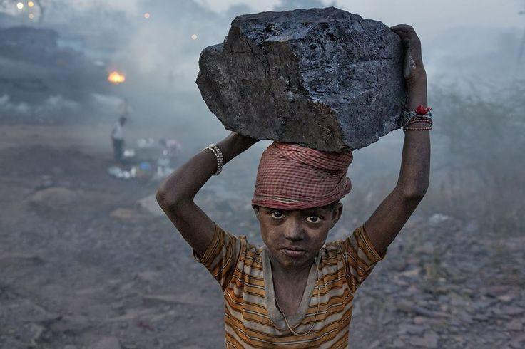 Ranchi, Jharkhand, India  Un ragazzo trasporta un pezzo di carbone nell'accampamento di minatori in cui vive. Fotografia di Robb Kendrick
