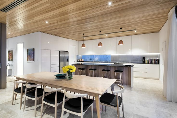 Minimalist kitchen with sleek white lacquer cabinetry & shadow-line of the American White Oak ceiling by custom home builder, Weststyle Design & Development featured in our 2016 edition of WA Custom Homes