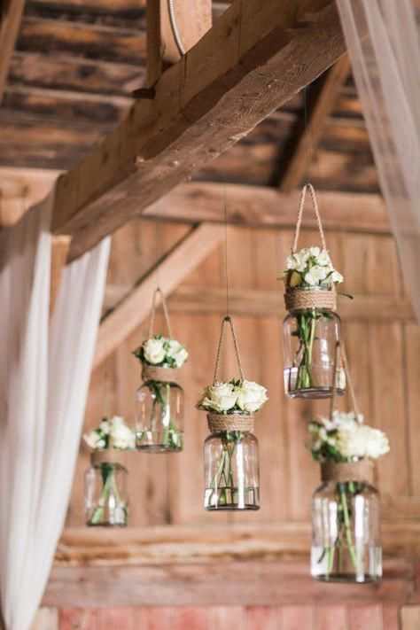 This rustic barn wedding nails county decor! We're loving how the decor included Mason jar flower holders and repurposed suitcases. #simplewedding