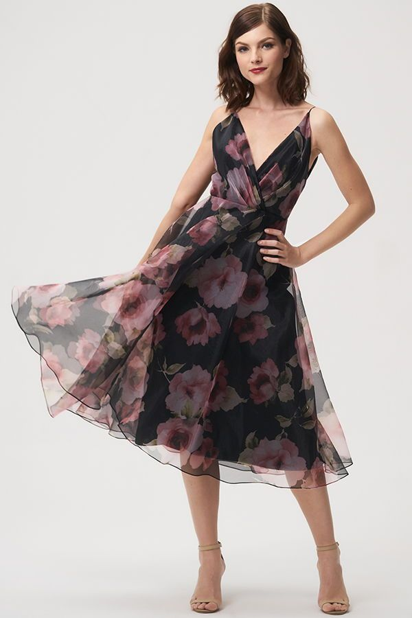 Jenny Yoo 2018 Bridesmaids, the short floral printed Sabrina dress features a surplice bodice with delicate spaghetti straps for a feminine silhouette. The taffeta circle skirt hits at midi tea length and billows out to create movement. V Neck. This dress is fully lined with a center back seam. Perfect for a cocktail event, garden, or summer wedding. Shown in Black Multi, available in Blush Multi.