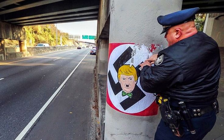 Trump voters deface Police posters with Trump stickers -- Police Officers in Bumshart Nebrahoma were furious to discover that recruitment posters around the town had been defaced with pictures of Donald Trump. The multi-million pound recruitment drive in the book free town of Bumshart was instigated two months ago. The plan isto recruit hundreds of ... -- #BlueShirts, #Swastika, #Trump -- http://wp.me/p7GOKB-1EW