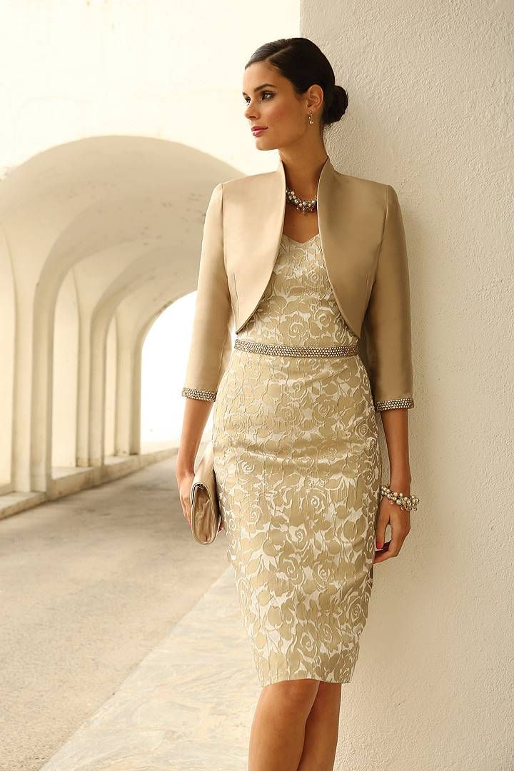 This 2-piece mother of the bride ensemble consists of a bolero jacket & jacquard dress with a gold shimmer. The belt accents the waist & the detail on the cuffs of the jacket makes it a perfect match with the dress. The earrings,  necklace, bracelet & bag are from our Linea Raffaelli Accessory collection