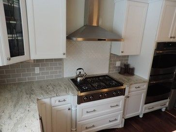 River White with Gray Ceramic Subway Backsplash , White Ceramic Arabesque Tiles, White Kitchen Cabinets and Stainless Steel Vent Hood