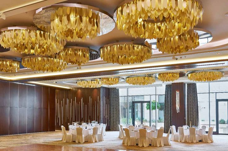 The conference hall, which can accommodate over 1000 guests, is equipped with nontraditional circular light fixtures where individual strips alternate filled and empty circles. These are made up of polished brass leaves with compelling details in the form of irregularly cut outer edges.