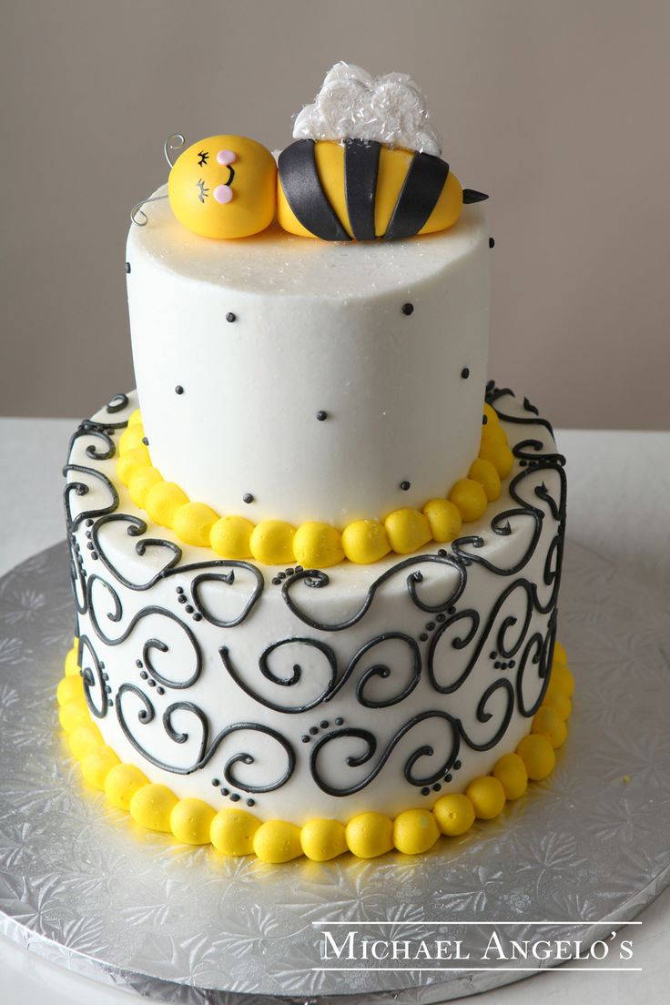 Bumble Bee Fast Asleep #34Baby This design is made of two tiers that are iced in buttercream. It is accented with black swirls and polka dots and match perfectly with the bee topper. This topper was handmade of gum paste. The wings were sprinkled with shimmer for a little glow.