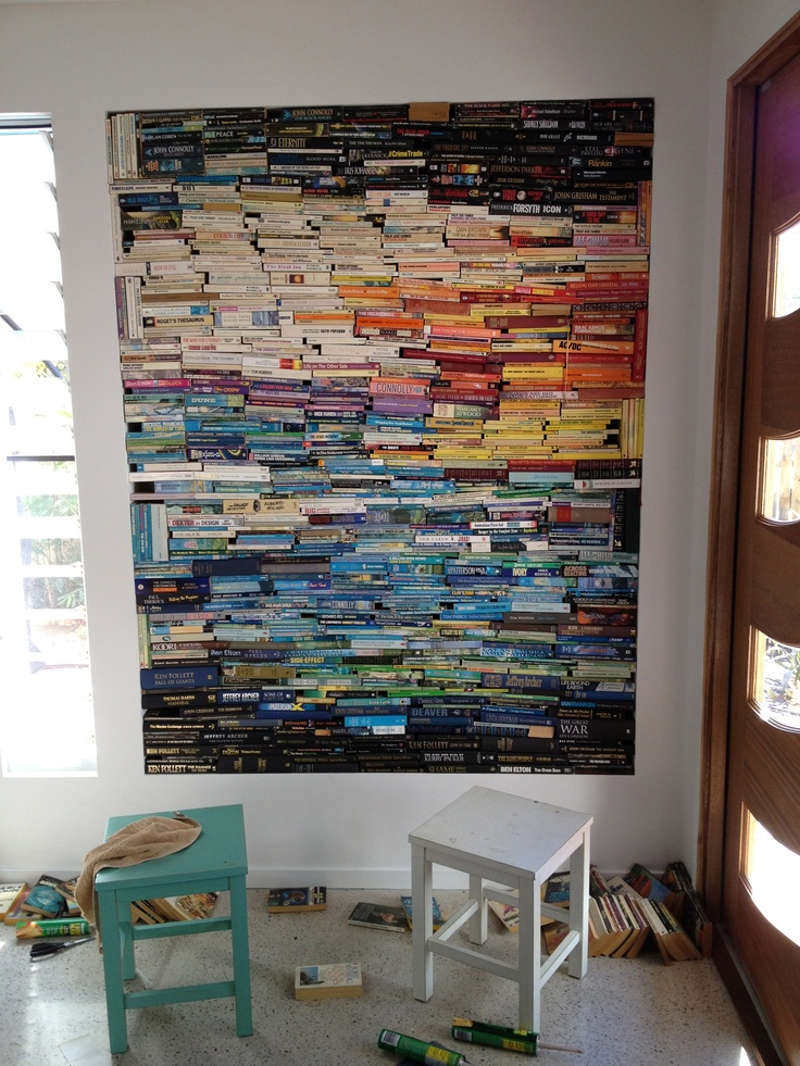 """Work in Progress - The first 2.1m x 2.1m recess in our house isn't really working as a display for my paintings since the large pivot door opens on to it.... thought I would put something different here ..... Our family has moved from books to EBooks, so have many books destined for the tip....  I have colour coded the spines and GLUED (eeek!) each book together to make a """"canvas"""" for my next piece.... watch this space for finished product!"""