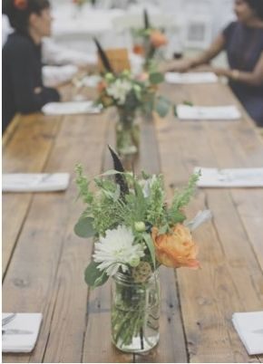 Long wooden plank wedding reception table with rustic centerpieces.