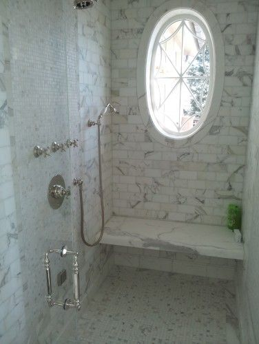 Calcutta subway tile shower with calcutta slab for shower seat; great shower door handle + Window!