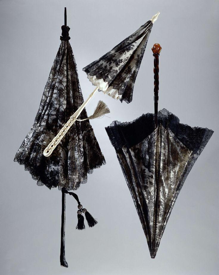 Anonymous | Bobbin lace parasol, Anonymous, c. 1860 - c. 1870 | Parasol met dek van zwart kloskant, met een patroon van negen bloemen boven een guirlande, een geschubde onderrand. Als ondergrond effen witte tafzijde. Voering van gebleekte katoen. De stok is van gesneden ivoor, met onderaan de vorm van schakels. Halverwege de stok rondom een klein acantusblad. Stalen baleinen. Aan de stok een kwast van satinet