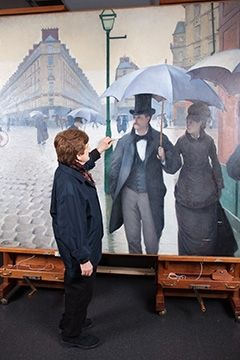 """Caillebotte """"Paris Street; Rainy Day"""" Returns-- Ongoing. Conservator Faye Wrubel uses a handmade cotton swab and a delicate cleaning solution to remove the yellowed varnish from Gustave Caillebotte's Paris Street; Rainy Day, 1877. Charles H. and Mary F. S. Worcester Collection."""