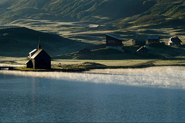 A chapel stands during morning sun next to the lake as mist rises from the water in the Melchsee-Frutt region in the central Alps in Switzerland.    Sigi Tischler/Keystone/AP