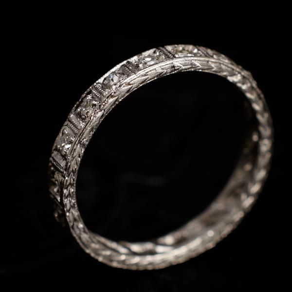 This pretty eternity ring is fashioned in platinum and dates to the early years of the Art Deco era. The bandsparkles with 18 .02ct single cut diamonds setwithin milgrain-edged squares. The north and south sides of the hoop are engraved with a wheat motif - a symbol of abundance and fertility. This ring is a size 4 and cannot be resized.    Materials: platinum, 18 x .02ct single cut diamonds  Age: c. 1925  Condition: Excellent  Size: US 4, cannot be resized; 2.6mm hoop  Location: To see…