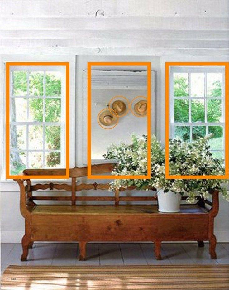 """Aprenda a usar a """"regra dos 3"""" para deixar a decoração da sua casa mais harmônica e aconchegante. Nesta foto o banco e o espelho ganham um terceiro elemento, o vaso deslocado para a direita, que dá vida ao conjunto. Um espelho é pendurado entre as duas janelas para funcionar como uma terceira janela e reflete os 3 chapéus pendurados na parede oposta."""