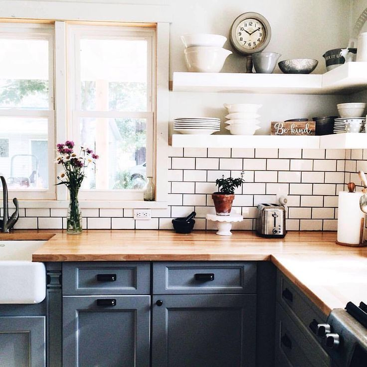 Open shelving, butcher block countertops and painted cabinets. Love the  dark grout with the subway tile.