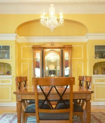 Yellow Dining Room With White Trim And Chandelier