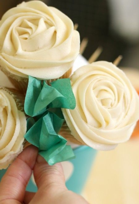 How to Make a Cupcake Bouquet:  You'll need: cupcakes, frosting, a disposable piping bag or a reusable piping bag, Wilton 1M tip (or a similar open star tip), green tissue paper, clear tape, flower pot, styrofoam ball, and toothpicks. All of these things are available online or at craft stores such as Michael's (that's where I found the adorable polka dot flower pot).