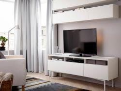 """Ein Wohnzimmer mit RAMSÄTRA TV-Bank und RAMSÄTRA Wandschränken in Weiß mit DIODER LED-Multibeleuchtung in Weiß, KARLSTAD Sessel mit Bezug """"Blekinge"""" in Weiß, TRÅL Stand-/Leseleuchte in Weiß und kurzflorigem STOCKHOLM Teppich in Braun"""