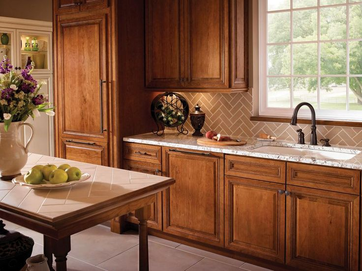 This country kitchen features warm cabinetry and herringbone-patterned tile backsplash. A large window allows natural light into the space, illuminating the neutral tones in the room.