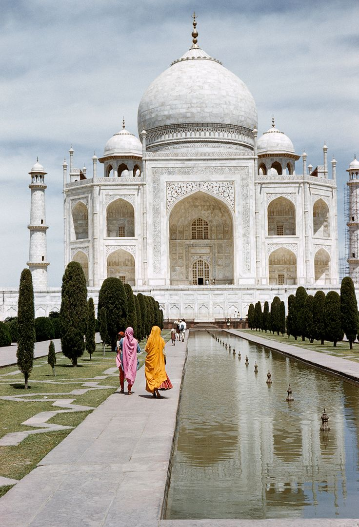 Women in bright dress walk by a fountain with the Taj Mahal in the background, 1959. Photograph by Melville B. Grosvenor, National Geographic Creative