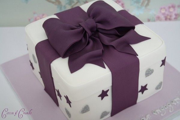 Birthday cake shaped like a gift box tied with a thick elaborate dark purple bow. The 'present' is decorated in a dark purple star and silver heart print.