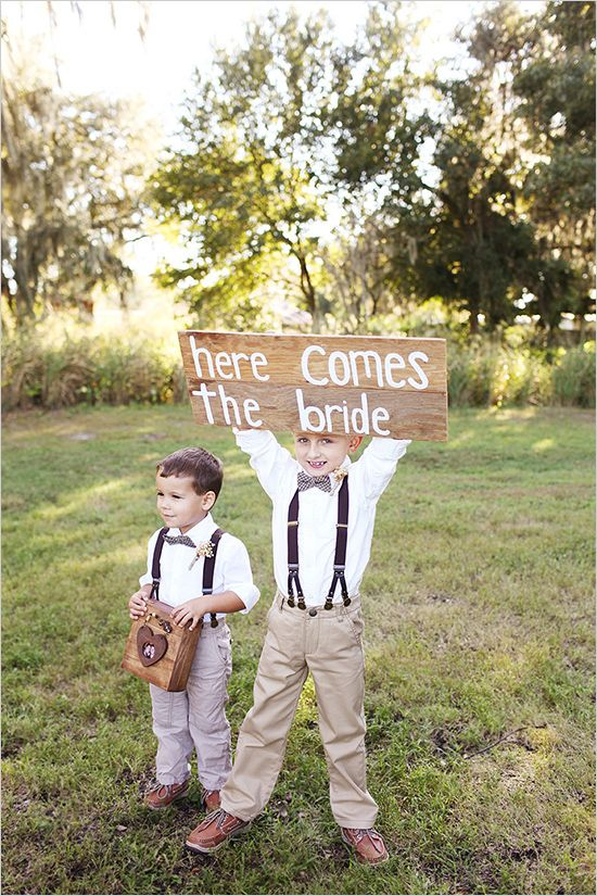 "Ring bearers in bow tie and suspenders with a wooden ""Here comes the bride"" sign. Captured By: Vine and Light Photography ---> http://www.weddingchicks.com/2014/05/14/soft-southern-vintage-wedding/"