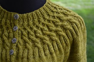 Richly colored yarn and a unique cable design at the hems and yoke combine for a classic cardigan with modern appeal.