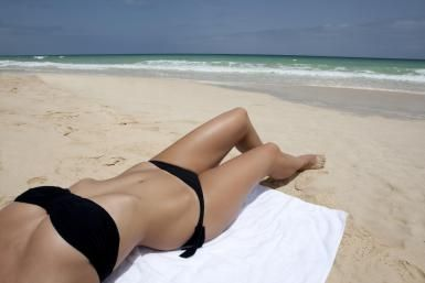 Woman in bikini sunbathing at beach - B2M Productions/Photographer's Choice RF/Getty Images