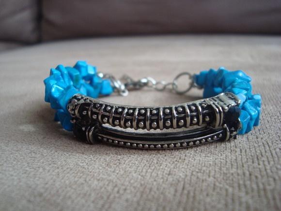 Pulseira confeccionada com cascalhos azul turquesa e peça central em metal, na cor prata velha, com aplicação de strass preto. R$30,00