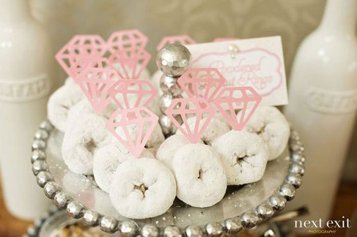 Attach a diamond-shaped cutout to a toothpick and spear through a powdered doughnut to transform the tiny dessert into a cute decoration. See more at Emmaline Bride.   - CountryLiving.com