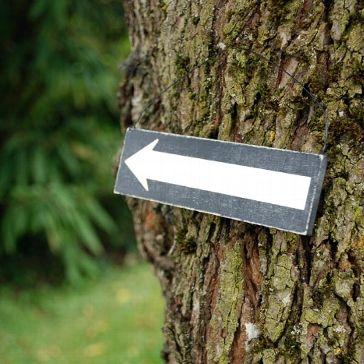 Schlichtes Holzschild mit Pfeil, um den Hochzeitsgästen auf simple Weise den Weg zur Hochzeit zu weisen.