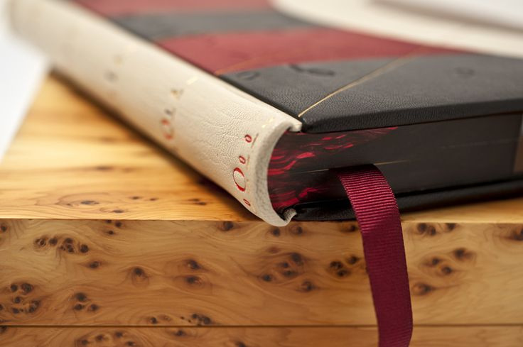 Titling in red on white leather with edge decoration and a silk ribbon? So beautifully coordinated, you can almost feel the love this book was made with.