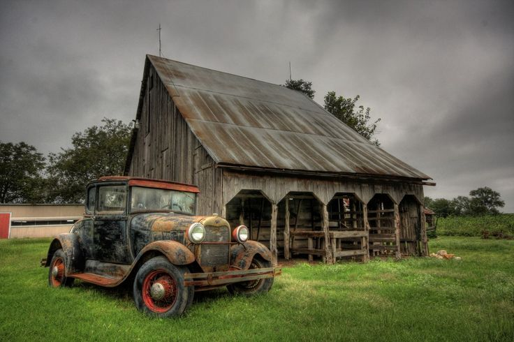 """1928-'29 Model A Ford coupe with '35 16"""" wire wheels, next to a Rustic Barn."""