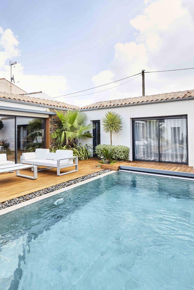 Une terrasse en bois exotique pour ce coin piscine ! De grandes baies vitrées pour amener de la luminosité dans le salon. Des palmiers et cactus pour apporter de la verdure. #menuiserierideau