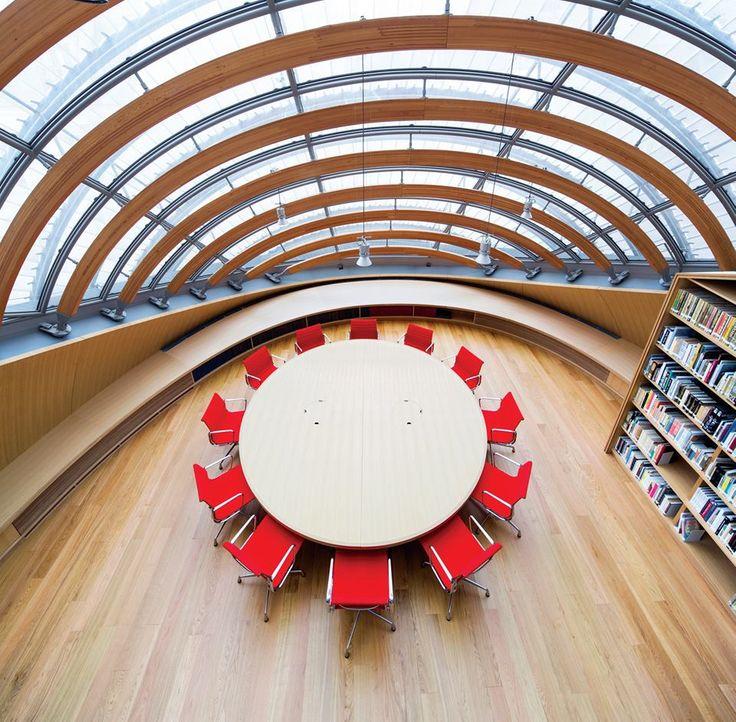 Deste ângulo, repare a estrutura da cobertura revestida de madeira, criando grandes arcos no teto, onde as luminárias foram instaladas.