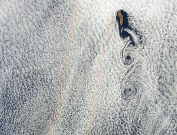 The two rainbows in this picture taken by an instrument on NASA's Aqua satellite are not actually rainbows at all but a phenomenon known as a glory. Glories and rainbows appear rather sumilar, but rainbows are formed by refraction and reflection, whereas glories are the result of backward diffraction. Glories tend to be circular rings of color, commonly seen from airplanes passing over thin clouds with droplets between 10 and 30 microns in diameter.