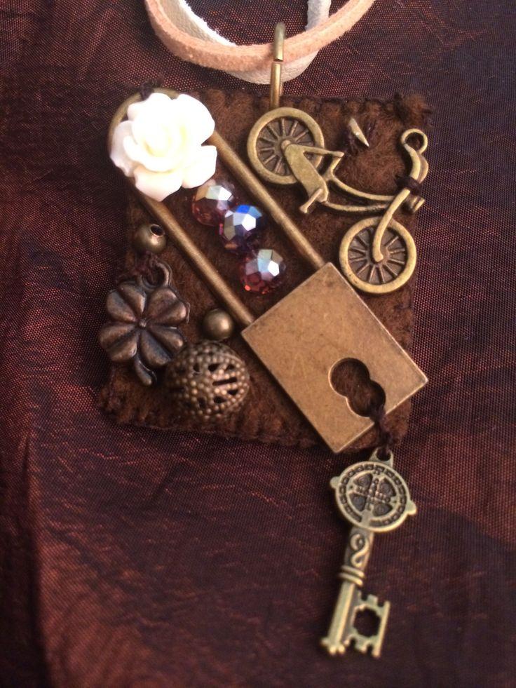 Dije bordado 100% a mano. Encantador candado con llave y bicicleta en acabado oro antiguo, cristales facetados y rosa de resina.
