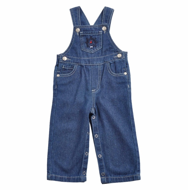 """Braga tipo """"overall"""" para bebe niño, confeccionada en algodón 100%, """"Jeans"""" en color azul. El peto de la Braga tiene un bolsillo con un timón bordado en colores azul oscuro, rojo y blanco. El peto tambien tiene botones para abotonar los tirantes y botones a los lados de la cintura. Dos bolsillos al frente y dos atras. Broches en la entrepierna."""