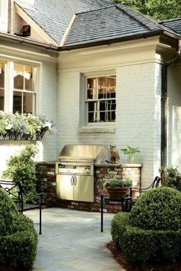 Outdoor grill surrounded by stone.   Love this outdoorspace, as well as the painted brick exterior