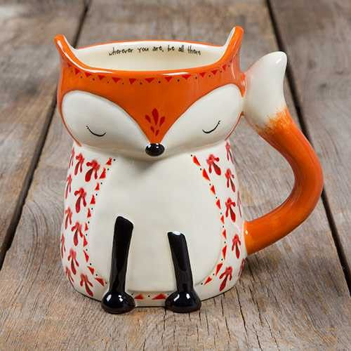 """This folk art mug will have you smiling every time you drink from it! It features an adorable fox design and the sweet sentiment, """"Wherever you are be all there"""" on the inside! This hand sculpted, cer"""