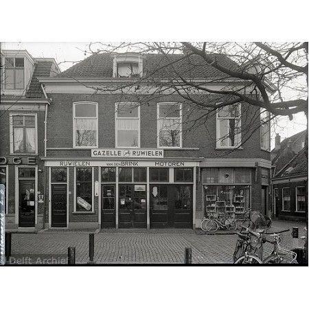 Delft, panden aan de Beestenmarkt. Rechts een kapper en op nummer 27 handel in rijwielen en motoren van Van den Brink. Circa 1960.