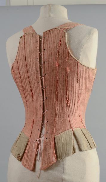Auction House Coutau-Bégarie -  Corps à baleines, début du XVIIIe siècle,en damas ramagé rose, piqûres rectilignes soulignant les baleines. Devant en pointe arrondie à effet de corset lacé matérialisé par des dentelles aux fuseaux en sorbec argent, basques gainées de peau. Laçage à oeillets dans le dos, (quelques usures).