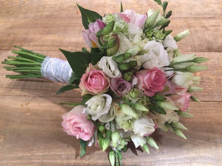 Rosas, lisianthus, fresia, en tonos rosas empolvados, blancos y verdes.