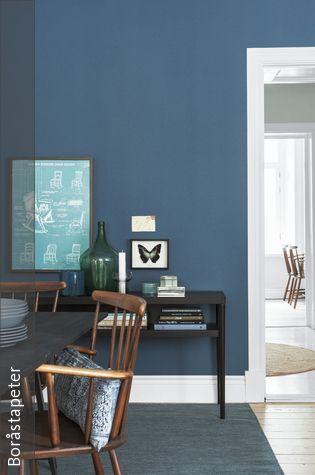 Vor dem Hintergrund der blauen Wandfarbe bekommen Wanddeko und Möbel besondere Aufmerksamkeit. Helle Wandbilder machen sich als Kontrast zur dunklen Farbe gut – aber auch dunkle Holzmöbel haben eine elegante Wirkung.