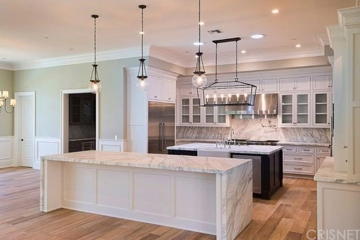 Light hardwood floors, white cabinets, two islands, glass accents, dark center island cabinets, white/grey counter tops