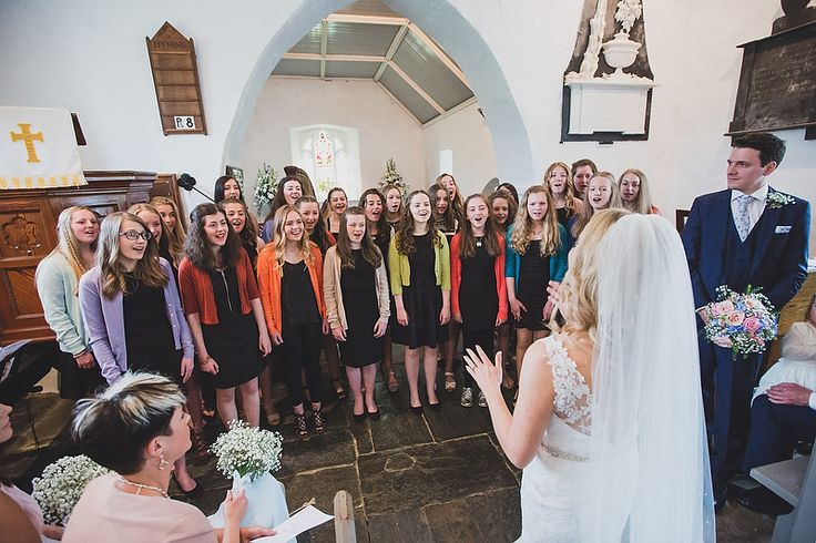 Make your wedding yours! This fabulous bride had her choir of school girls extremely well trained, but couldn't help stopping to conduct them herself for a moment before they sang her down the aisle. :) Spring wedding at Cliff Hotel by Whole Picture Weddings
