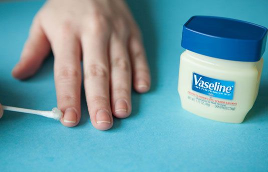 If you're working on a nail look that's messy, use a cotton swab to rub petroleum jelly like Vaseline on the skin around your nails first.This creates a barrier between the polish and your skin so that after you've painted your nails, you can wipe off the Vaseline and any polish mistakes along with it.